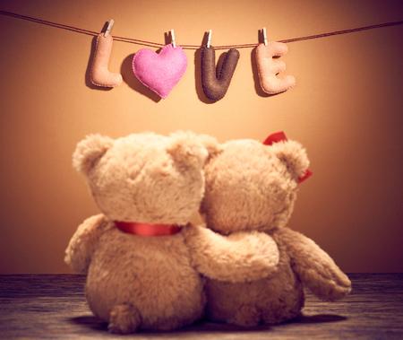 Valentijnsdag. Word Love heart. Paar Teddy Bears in omhelzing, het koesteren, datum. Handgemaakt. Vintage retro romantische stijl. Ongebruikelijke creatieve wenskaart op hout, vanille. Familie, huwelijk en vriendschap Stockfoto
