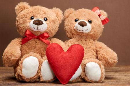 parejas romanticas: Día de San Valentín. Amor corazon. Pareja de osos de peluche en el abrazo, abrazos. corazón rojo hecho a mano, cinta, arco. Tarjeta de la vendimia retro romántico style.Unusual creativa saludo en la madera. La familia, la boda y la amistad