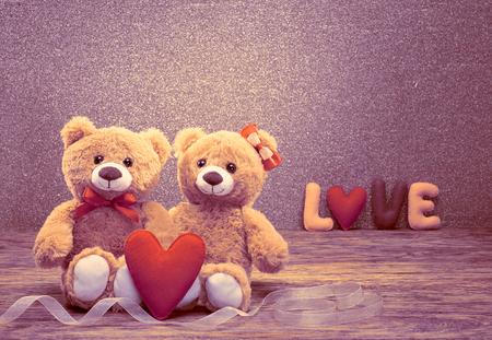 Valentijnsdag. Word Love heart. Paar Teddy Bears in omhelzing, knuffelen. Handgemaakte rood hart. Vintage retro romantische stijl. Ongebruikelijke creatieve wenskaart op hout, glanzend. Familie, huwelijk en vriendschap Stockfoto