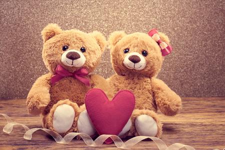 parejas de amor: Día de San Valentín. Amor corazon. Pareja osos de peluche en el abrazo, abrazos. Hecho a mano corazón rosa, arco. Tarjeta de la vendimia retro romántico style.Unusual creativa saludo en madera, brillante. Familia, la boda y la amistad Foto de archivo
