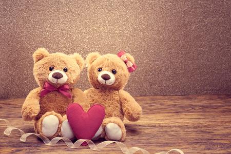 Día de San Valentín. Amor corazon. Pareja osos de peluche en el abrazo, abrazos. Hecho a mano corazón rosa, arco. Tarjeta de la vendimia retro romántico style.Unusual creativa saludo en madera, brillante. Familia, la boda y la amistad Foto de archivo