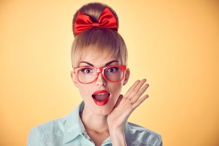 Beauty mode portret zakenvrouw, stijlvolle rode bril verrast, mond open, geschokt. Aantrekkelijke blonde meisje, vertrouwen, Pinup kapsel boog makeup.Unusual speels, emotions.Vintage, op geel Stockfoto