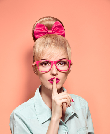 stereotypical: Beauty fashion nerdy woman in stylish glasses thinking, idea. Attractive pretty funny blonde girl smiling. Confidence, success, Pinup hairstyle bow makeup. Unusual playful, expression.Vintage, on pink Stock Photo
