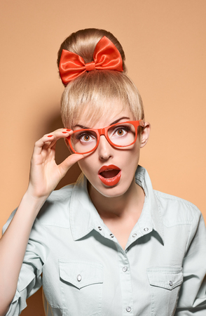 Beauty fashion portrait woman in stylish glasses surprised. Attractive pretty blonde sexy hipster girl. Confidence, success, Pinup hairstyle, trendy red bow.Unusual playful, creative. Vintage, vanilla Zdjęcie Seryjne