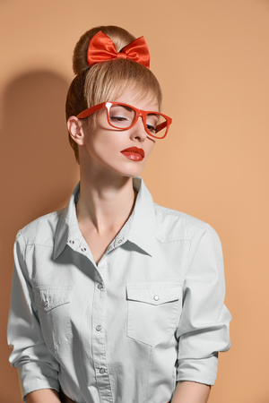 stereotypical: Beauty fashion woman in stylish glasses thinking, idea. Attractive pretty blonde hipster girl smiling. Confidence, success, Pinup hairstyle,red bow makeup. Unusual playful, expression.Vintage, vanilla