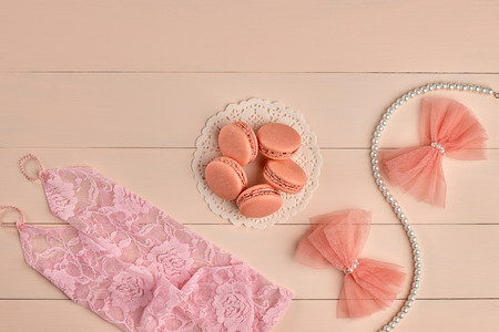 lace gloves: Overhead woman essentials fashion wedding accessories set. Lace pink gloves, macarons french dessert, pearl necklace, bows.Creative bride set, vanilla wooden background. Romantic, still life.Top view