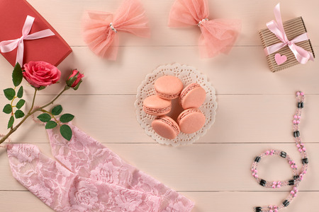 lace gloves: Overhead woman essentials fashion wedding accessories set. Lace gloves, macarons, gift boxes, necklace and roses. Creative bride set, vanilla wooden background. Romantic modern, still life. Top view Stock Photo