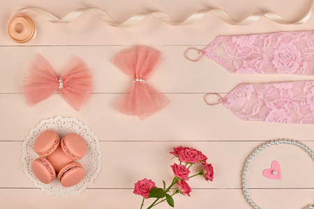 lace gloves: Overhead woman essentials fashion wedding accessories set. Lace gloves, macarons, gift box, pearl necklace, roses. Creative bride set, vanilla wooden background. Romantic modern, still life. Top view Stock Photo