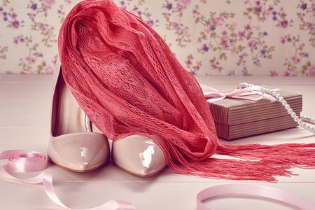 여성 패션 액세서리 필수품. 고급 베이지 색 신발 하이힐, 분홍색 스카프, 진주 목걸이, 리본, 선물. 크리 에이 티브 웨딩 세트, 바닐라 나무, 꽃 back