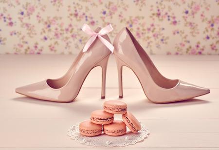 Vrouw essentials mode-accessoires. Macarons frans dessert, luxe beige schoenen met hoge hakken, parel, boog. Creatief huwelijk set, vanille hout, bloemen achtergrond. Romantisch, stilleven. retro vintage