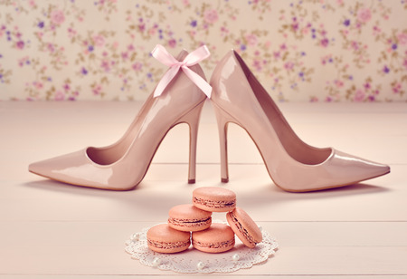 Woman essentials fashion accessories. Macarons french dessert, luxury beige shoes high heels, pearl, bow. Creative wedding set, vanilla wood, floral background. Romantic, still life. Retro vintage