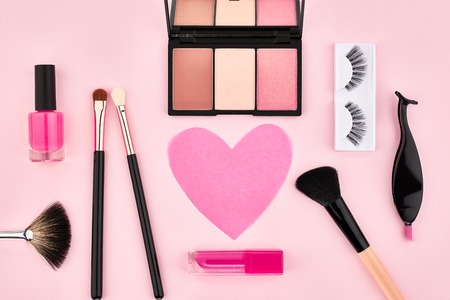 life styles: Overhead Still life, fashion woman essentials cosmetics. Beauty makeup accessories. Lipstick, brushes, eyeshadow, false eyelashes, heart. Unusual creative set. Pink background, top view