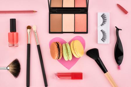 Overhead Still life, fashion woman essentials cosmetics. Beauty makeup accessories.Macarons french dessert. Lipstick, brushes, eyeshadow, false eyelashes.Unusual creative set.Pink background, top view 版權商用圖片