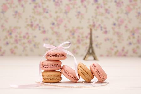 마카롱 프랑스 디저트. 에펠 탑, 파리, 신선한 파스텔 디저트, 핑크 리본에서 기념품. 크리 에이 티브 웨딩 세트, 바닐라 나무, 꽃 배경입니다. 로맨틱,