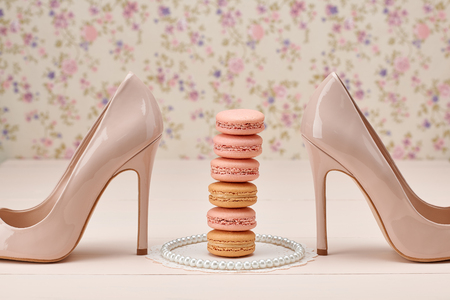 Woman essentials fashion accessories. Macarons french dessert, pearl necklace, luxury beige shoes high heels. Creative wedding set, vanilla wood, floral background. Romantic, still life.Retro vintage