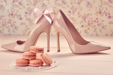 Still life. Woman essentials fashion accessories. Macarons french dessert, luxury beige shoes high heels, pearl, bow. Creative wedding set, vanilla wood, floral background. Romantic, retro vintage Banco de Imagens