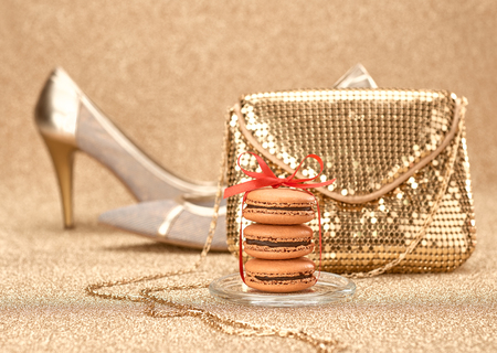 handbag: Macarons french dessert. Still life. Luxury shiny shoes high heels, glamor fashion handbag clutch, red ribbon. Vintage retro romantic. Unusual creative art greeting card, gold party background, bokeh Stock Photo