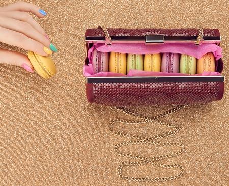 copyspase: Macarons french in handbag, woman hand. Luxury shiny glamor fashion clutch. Sweet colorful dessert. Unusual creative art, gold party background, bokeh, copyspase. Vintage Stock Photo