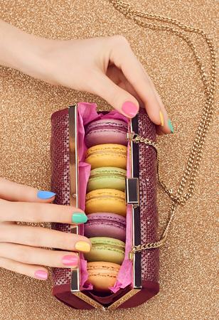 copyspase: Macarons french in handbag, woman hands. Luxury shiny glamor fashion clutch. Sweet colorful dessert. Unusual creative art, gold party background, bokeh, copyspase. Vintage