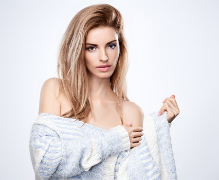 Beauty fashion portrait woman sensually looks, stylish warm knitted sweater. Attractive pretty blonde sexy model girl, shiny straight hair. Unusual creative provocative. Emotional playful people