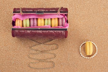 copyspase: Macarons french in handbag. Luxury shiny glamor fashion clutch. Sweet colorful dessert. Unusual creative art, gold party background, bokeh, copyspase. Vintage
