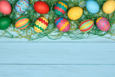 painted background: Easter eggs background. Hand painted multicolored decorated eggs on green straw, blue wood, copyspace. Unusual creative holiday greeting card