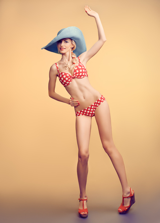 red and blue: Sexy PinUp woman in fashion red polka dots swimsuit, blue hat, beach slim body. Playful blonde girl in bikini smiling. Summer holiday, sea vacation. Yellow, vintage toned, unusual creative provocative