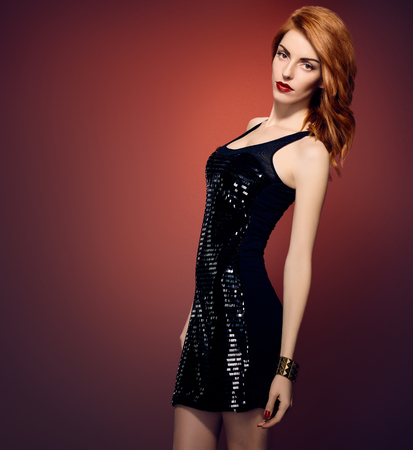 provocative woman: Fashion portrait of sexy beauty woman in stylish sequins dress and black hat. Unusual creative provocative. Emotional playful redhead glamour girl, luxury evening elegant party style on red, people