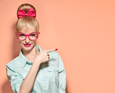 nerd glasses: Beauty fashion woman in stylish glasses shows finger. Attractive happy blonde hipster girl smiling, emotional. Confidence, success, Pinup hairstyle. Unusual playful, expression nerd. Vintageon pink