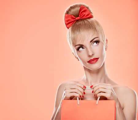 nude caucasian: Beauty fashion portrait loving woman thinking with shopping bag. Confidence sensual attractive pretty nude blonde sexy girl, Pinup hairstyle, red bow. Unusual playful. Romantic on pink, sale, discount