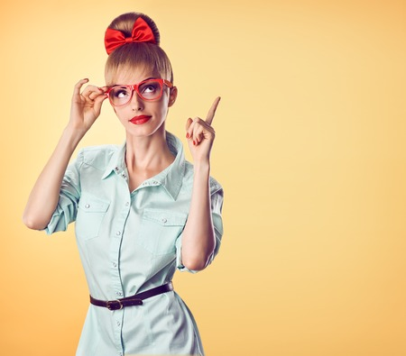 Beauty fashion nerd woman in stylish glasses thinking, idea. Attractive pretty funny blonde girl smiling.Confidence, success, Pinup hairstyle bow makeup.Unusual playful, expression.Vintage, on yellow 版權商用圖片
