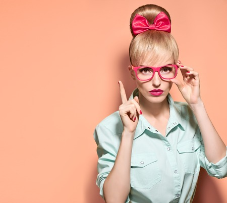 stereotypical: Beauty fashion woman in stylish glasses thinking, idea. Attractive happy blonde hipster girl smiling, emotional. Confidence, success, Pinup hairstyle. Unusual playful, expression nerd.Vintage on pink