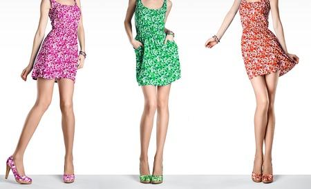 Vrouw in de mode vintage jurk en hoge hakken. Vrouw sexy lange benen, stijlvolle kleurrijke bloem sundress en zomerschoenen. Meisje in verschillende speelse poses. Ongebruikelijke creatieve lopen uit uitrusting, mensen