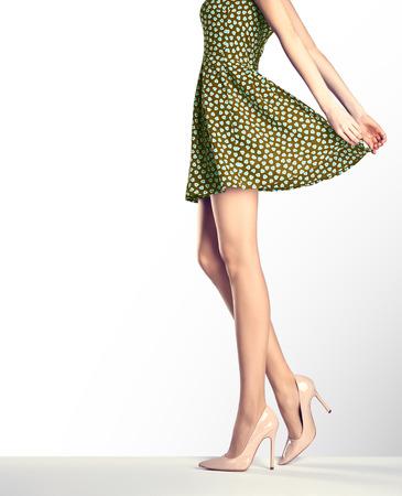 Vrouw in mode vintage jurk en hoge hakken. Perfecte vrouwelijke sexy lange benen, stijlvolle groene rok en zomer glamour schoenen. Ongebruikelijke creatieve elegante wandeltoestellen, mensen. Vintage, kopieer ruimte