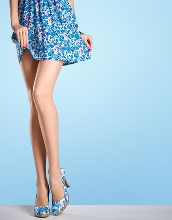 패션 드레스, 하이힐 여자 긴 다리. 완벽한 여성의 섹시한 다리, 세련된 블루 플라워 스커트와 여름 매력적인 신발입니다. 특이 창조적 인 우아한 산책