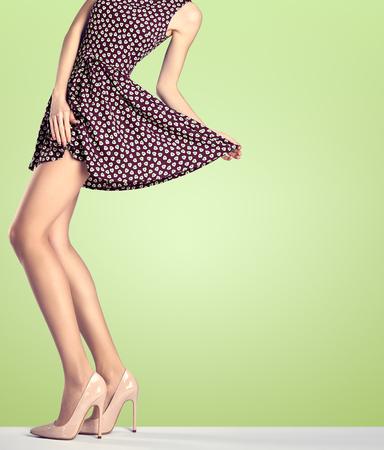 Vrouw in de mode vintage jurk en hoge hakken. Perfecte vrouwelijke sexy lange benen, stijlvolle rode rok en de zomer glamour schoenen op groen. Ongebruikelijke creatieve elegant lopen uit uitrusting, mensen. Kopieer de ruimte