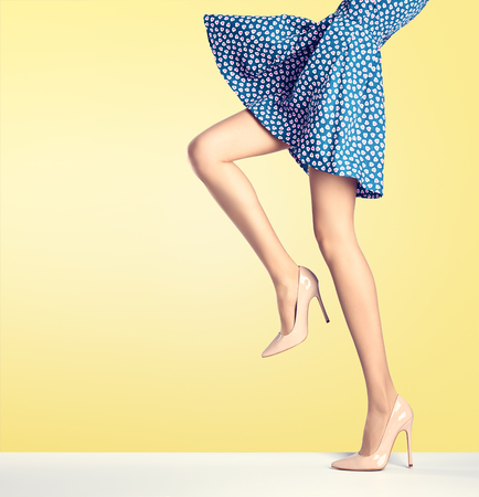 女性ファッションのドレス、ハイヒールの足が長い。完璧な女性のセクシーな脚、スタイリッシュな青いスカートと黄色の夏グラマー靴。異常な創