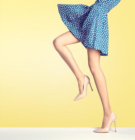 Vrouw lange benen in de mode jurk, hoge hakken. Perfecte vrouwelijke sexy benen, stijlvolle blauwe rok en de zomer glamour schoenen op geel. Ongebruikelijke creatieve elegant lopen uit uitrusting, mensen. Vintage, kopie ruimte