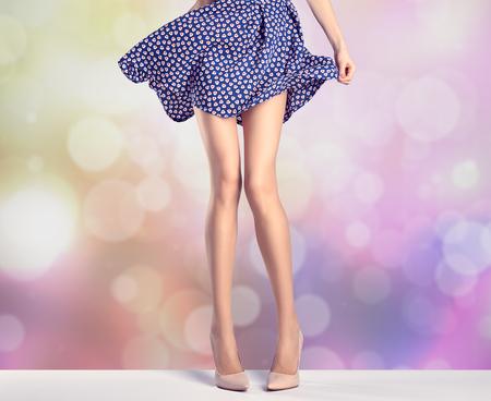 女性ファッションのドレス、ハイヒールの足が長い。完璧な女性のセクシーな脚、スタイリッシュな紫のスカート、夏グラマー靴、カラフルな抽象