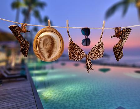 해변 복장. 여름 옷 및 액세서리 세련 된 설정합니다. 패션 수영복 비키니, 선글라스, 발 뒤꿈치 모자. 열대성 파티, 바다 하늘 background.Sunset, 바다 휴가 스톡 콘텐츠