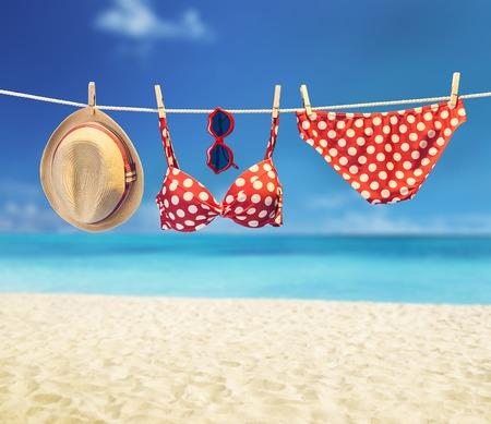 lunares rojos: traje de playa. ropa y accesorios de verano elegante conjunto. La moda del traje de ba�o del bikini de lunares rojo, gafas de sol sombrero. Fundamentos mirada creativa en background.Hawaii cielo mar tropical, oc�ano vacation.Vintage Foto de archivo