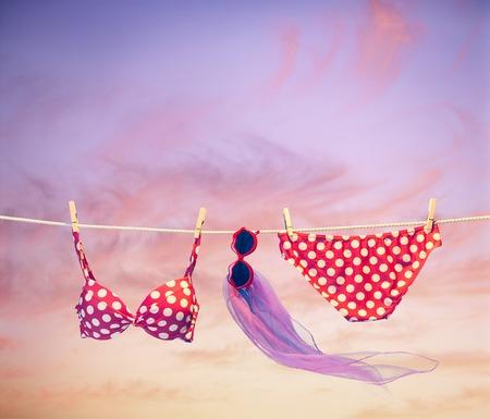 red polka dots: traje de playa. ropa y accesorios de verano elegante conjunto. Moda de baño bikini de lunares rojo, gafas de sol. EssEntials mirada creativa en el fondo de cielo mar tropical. Sunset vacaciones océano. Vendimia Foto de archivo