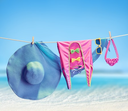 pareo: Beach outfit. Summer clothes and accessories stylish set. Fashion swimsuit, sunglasses, hat and pareo on rope. Essentials creative look on tropical sea sky background. Hawaii, ocean vacation concept Stock Photo