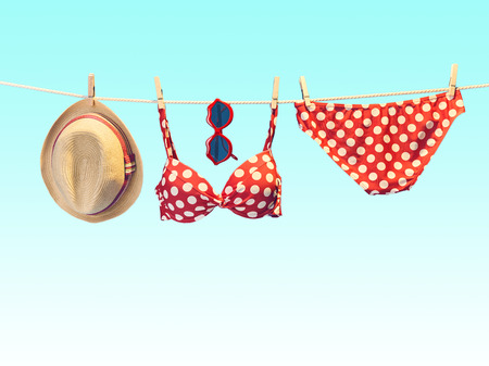 Beach outfit. Summer clothes and accessories stylish set. Fashion swimsuit bikini red polka dots, sunglasses, hat on rope. Essentials creative tropical look on blue. Ocean sea vacation concept,vintage