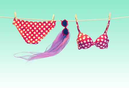 lunares rojos: traje de playa. ropa y accesorios de verano elegante conjunto. La moda del traje de ba�o del bikini de lunares rojo, gafas de sol en la cuerda. Fundamentos de aspecto tropical creativo en azul. Oc�ano concepto de vacaciones de mar, de la vendimia Foto de archivo