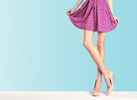 女性ファッションのドレス、ハイヒールの足が長い。完璧な女性のセクシーな脚、スタイリッシュな赤いスカート、ブルーで夏グラマー靴。異常な 写真素材