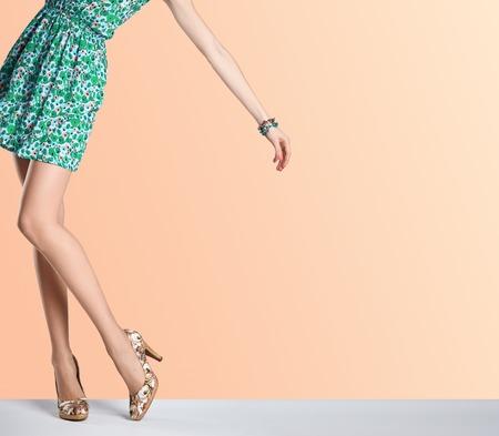 Vrouw in de mode jurk en hoge hakken. Vrouw sexy lange benen, stijlvolle groene bloem sundress en de zomer glamour schoenen op oranje. Ongebruikelijke creatieve elegant lopen uit uitrusting, mensen. Vintage, kopie ruimte Stockfoto