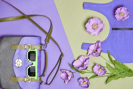 Summer Fashion vrouw ingesteld, accessoires. Creative hipster look, pastelkleuren. Stijlvolle handtas, kleding, zonnebrillen en flowers.Unusual stedelijke benodigdheden. Overhead outfit. Bovenaanzicht, paars groene achtergrond Stockfoto