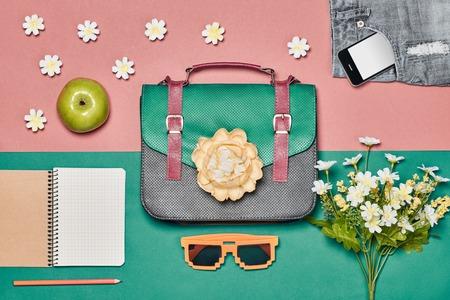 Komplet damski z lato, dodatki. Kreatywny wygląd hipster, pastelowe kolory. Torebka, okulary przeciwsłoneczne, smartphone, jabłko i kwiaty. Nad głową. Nietypowe essentials.Top widok, różowe tło