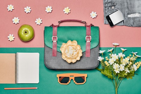 Summer Fashion ladies set, accessories. Creative hipster look, pastel colors. Handbag, shorts sunglasses, smartphone, apple and flowers. Overhead. Unusual essentials.Top view, pink background